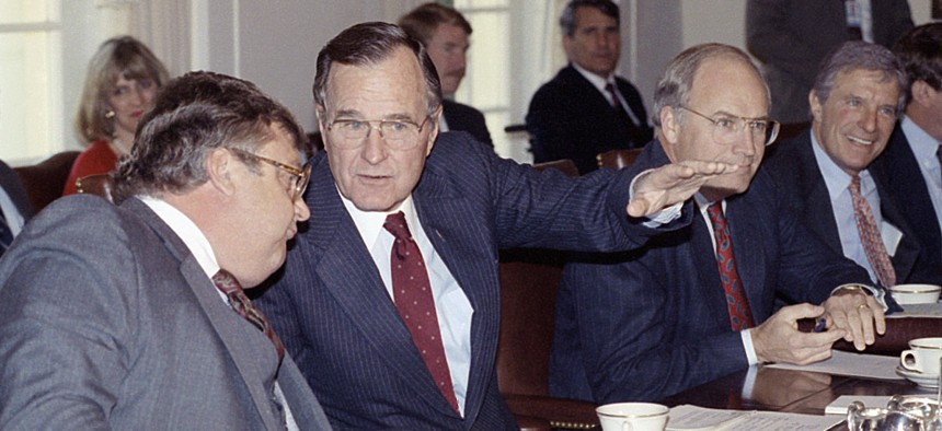 In this Nov. 13, 1990 photo, President George H. Bush talks with Deputy Secretary of State Lawrence Eagleburger at the start of Cabinet meeting at the White House in Washington.