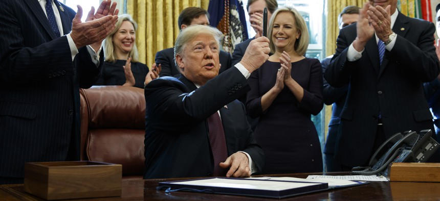 """President Donald Trump holds up a pen during a signing ceremony of the """"Cybersecurity and Infrastructure Security Agency Act,"""" in the Oval Office of the White House, Friday, Nov. 16, 2018, in Washington."""