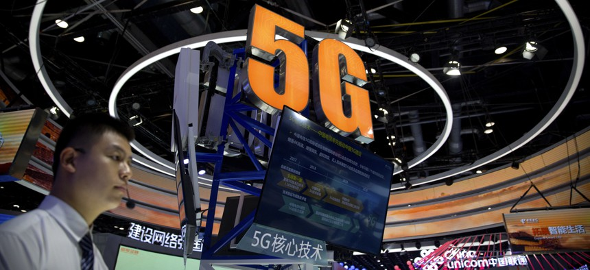 A staff member stands at a display for 5G wireless technology from Chinese firm China Telecom at the PT Expo in Beijing, Wednesday, Sept. 26, 2018.