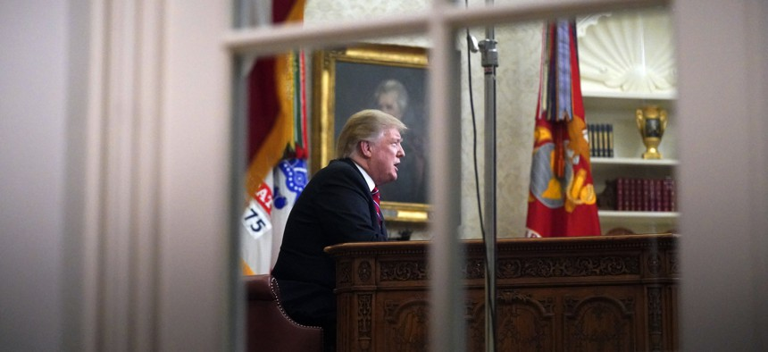 As seen from a window outside the Oval Office, President Donald Trump gives a prime-time address about border security Tuesday, Jan. 8, 2018, at the White House in Washington.