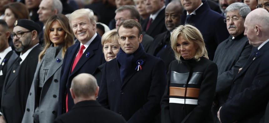 Russian President Vladimir Putin, back to camera, arrives to take his seat with French President Emmanuel Macron, Brigitte Macron, German Chancellor Angela Merkel, and U.S. President Donald Trump in Paris on Nov. 11, 2018.