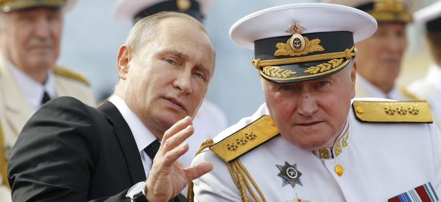 Russian President Vladimir Putin, left, chats with Commander-in-Chief of the Russian Navy Admiral Vladimir Korolev as they attend the military parade during the Navy Day celebration in St.Petersburg, Russia, on Sunday, July 30, 2017.