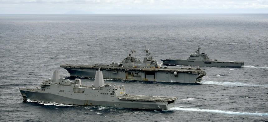 The amphibious transport dock ship USS Green Bay (LPD 20), left, amphibious assault ship USS Wasp (LHD 1), and Japan Maritime Self-Defense Force amphibious transport dock ship JS Kunisaki (LST 4003) transit in formation during a cooperative deployment.