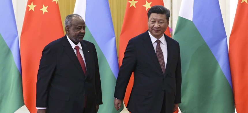 Djibouti's President Ismail Omar Guelleh, left, and Chinese President Xi Jinping walk for their bilateral meeting at the Great Hall of the People in Beijing, Sunday, Sept. 2, 2018.