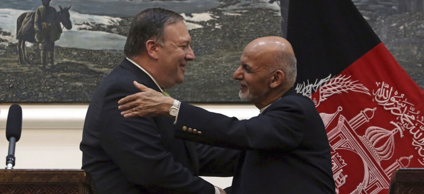 U.S. Secretary of State Mike Pompeo, left and Afghan President Ashraf Ghani, shake hands after a press conference at the presidential palace in Kabul, Afghanistan, Monday, July 9, 2018.