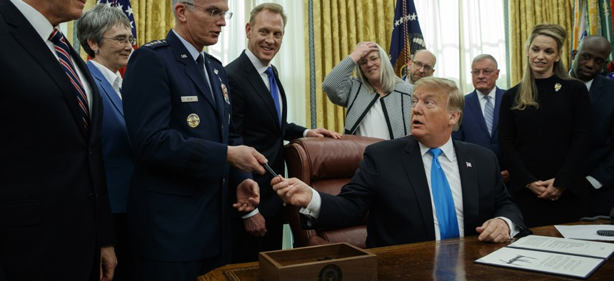 """President Donald Trump hands a pen to Air Force Gen. Paul Selva after signing """"Space Policy Directive 4"""" in the Oval Office of the White House, Tuesday, Feb. 19, 2019, in Washington."""