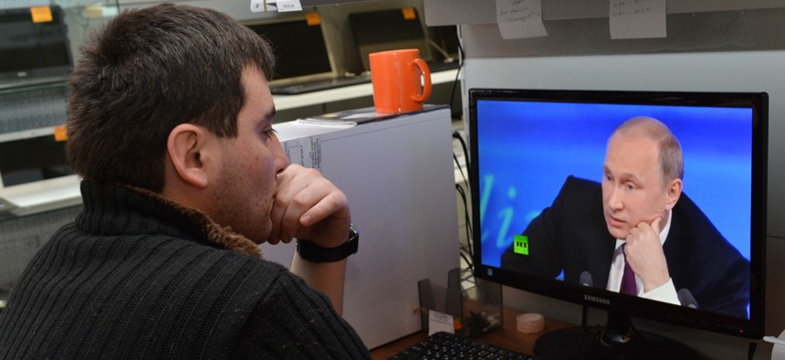 A customer watches Russian President Vladimir Putin on a computer screen in an electronic hypermarket in Grozny, regional Chechen capital, Russia, Thursday, Dec. 18, 2014.