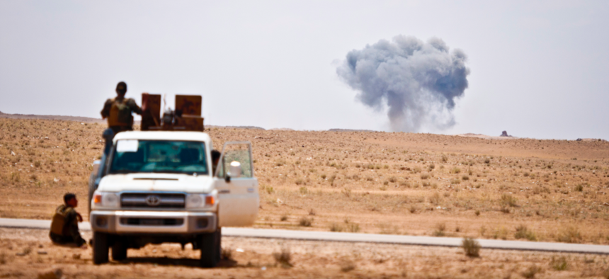 Syrian Democratic Forces watch as a Coalition airstrike hits its target on a known ISIS location near the Iraqi-Syrian border, May 13, 2018.