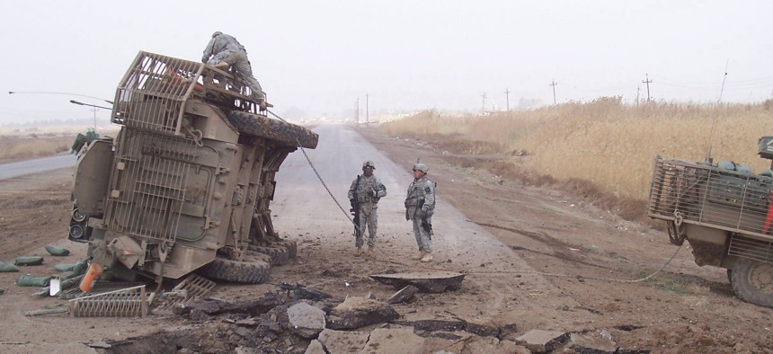 A Stryker fighting vehicle lies on its side after surviving a buried IED blast in 2007.