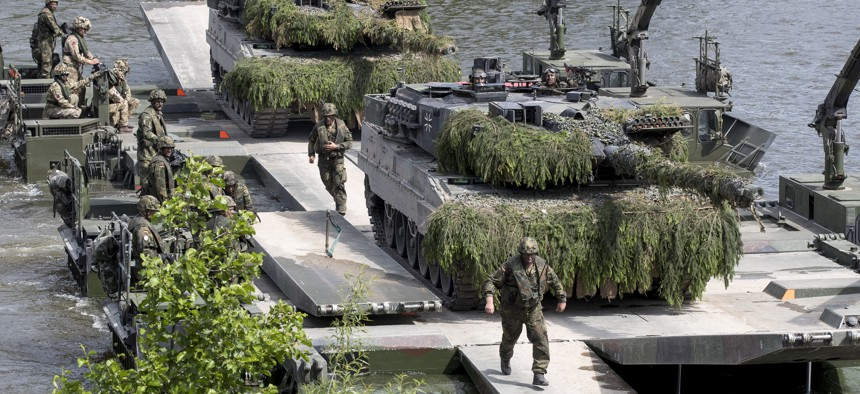 German Army soldiers dismantle a bridge over the Neris river during the NATO military exercise 'Iron Wolf 2017' at the village Stasenai, some 130kms (80 miles) west-north of the capital Vilnius, Lithuania, Tuesday, June 20, 2017.