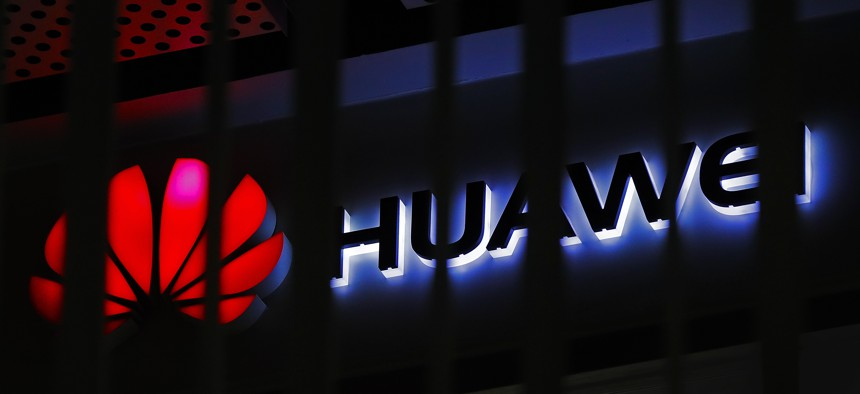 In this March 8, 2019, file photo, A logo of Huawei retail shop is seen through a handrail inside a commercial office building in Beijing.