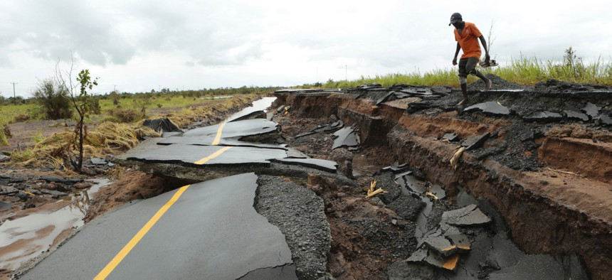 A man passes through a section of the road damaged by Cyclone Idai in Nhamatanda about 50 kilometres from Beira, in Mozambique, Friday March, 22, 2019.