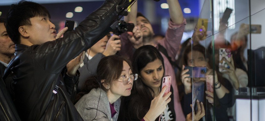 Attendees take pictures of the new Huawei Mate X foldable 5G smartphone during the Mobile World Congress wireless show, in Barcelona, Spain, Monday, Feb. 25, 2019.