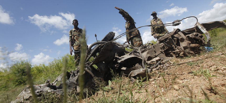 Somali soldiers stand near the wreckage of car bomb at a Somali military base near the site of the attack by al-Shabab in which a US soldier was killed and four others were injured.