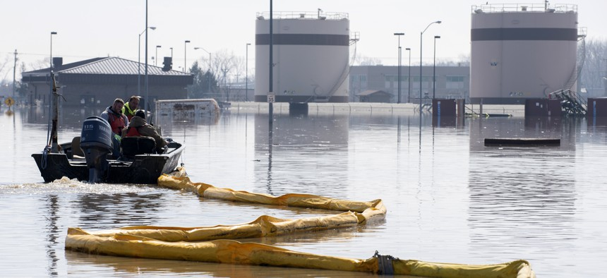 In this March 18, 2019 file photo released by the U.S. Air Force, environmental restoration employees deploy a containment boom from a boat on Offutt Air Force Base in Nebraska, as a precautionary measure for possible fuel leaks in the flooded area.