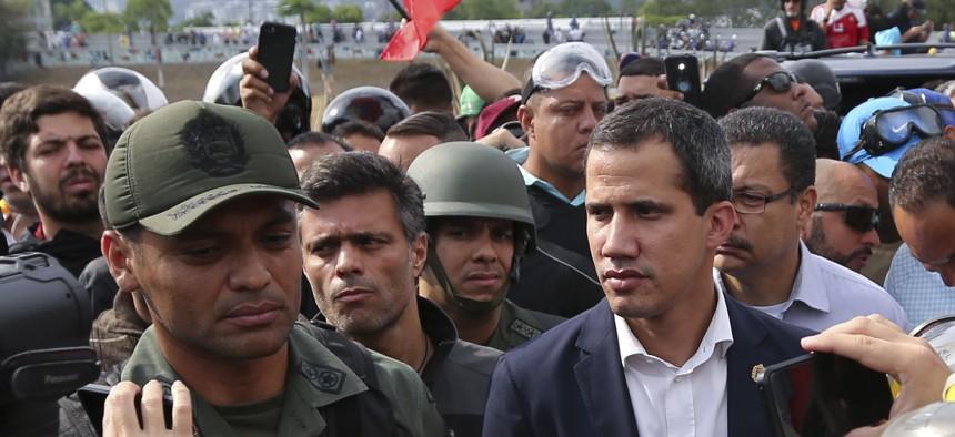 Venezuela's opposition leader Juan Guaidó, center right, flanked by activist Leopoldo López, center left, stands with National Guard Lieutenant Colonel Ilich Sanchez, outside La Carlota air base in Caracas, Venezuela, Tuesday, April 30, 2019.