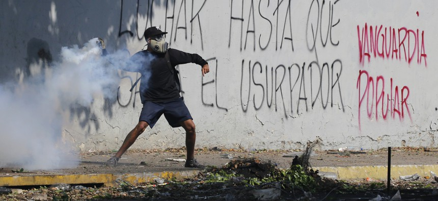 An anti-government protester winds up to return a tear gas canister launched by security forces to disperse demonstrators in Caracas, Venezuela, Wednesday, May 1, 2019.