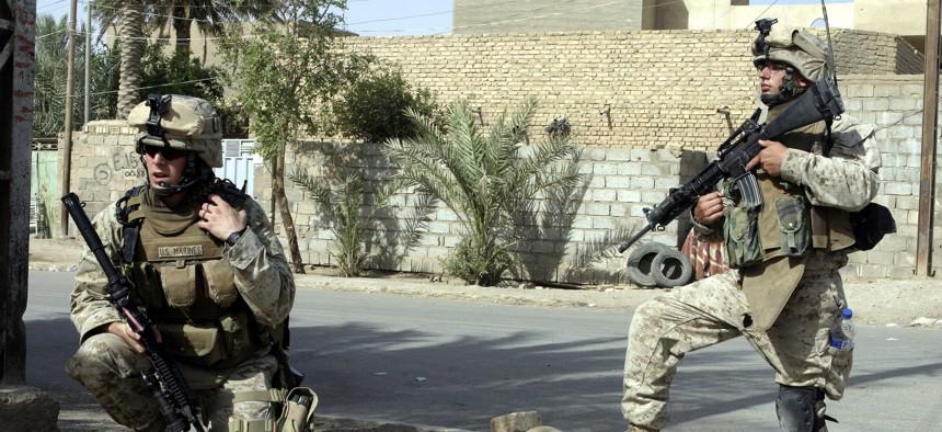 Second Lt. Joseph Davis of the 6th Marine Regiment, left, talks on the radio in Fallujah, Iraq, in 2005.