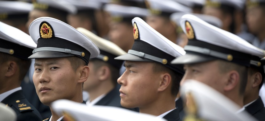 Chinese sailors sit before the start of a concert featuring Chinese and foreign military bands in Qingdao, Monday, April 22, 2019.