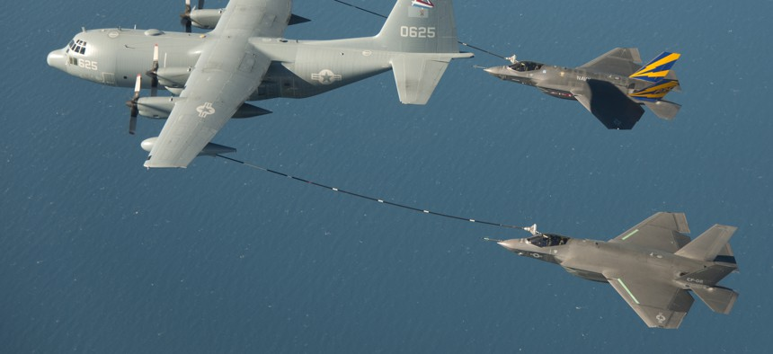 Two F-35 fighter jets take on fuel in midair.