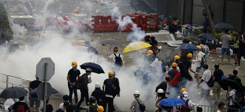 In this June 12, 2019, file photo, riot police fire tear gas toward protesters outside the Legislative Council in Hong Kong.
