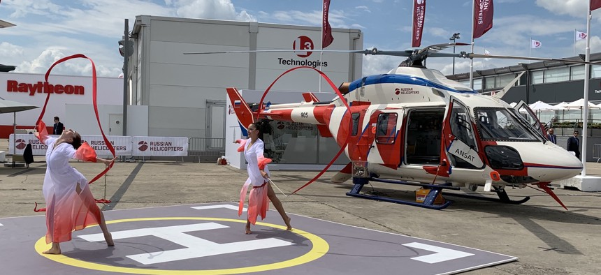 Dancers perform next to Russian Helicopters' Ansat light helicopter at the 2019 Paris Air Show.