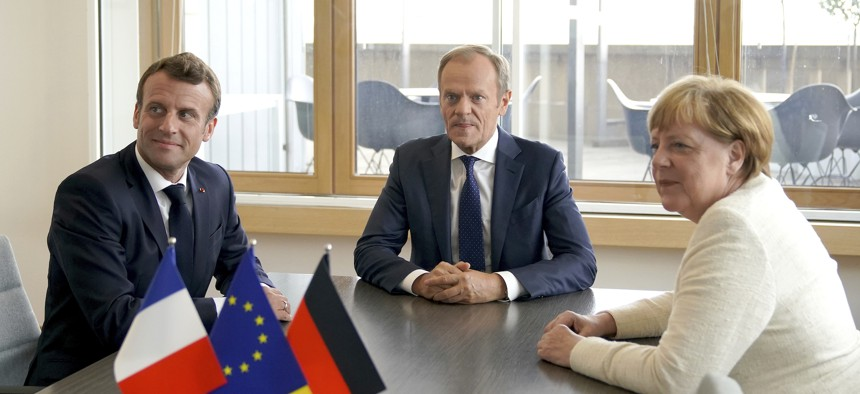 European Council President Donald Tusk, center, and German Chancellor Angela Merkel meet on the sidelines of an EU summit in Brussels, Thursday, June 20, 2019