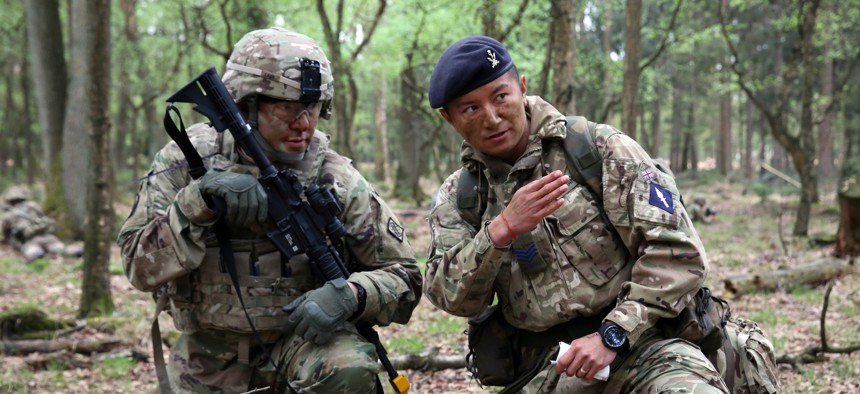 British Army Sgt. Thapa Kumar instructs U.S. Army Staff Sgt. Jeffery Lamb during a joint tactical patrol during exercise Stoney Run in the Sennelager Training Area, Germany, April 24, 2018.