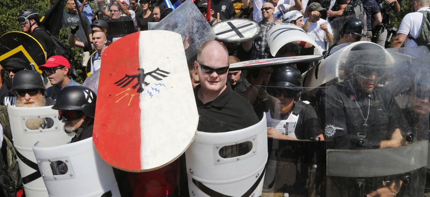 In this Aug. 12, 2017, file photo, white nationalist demonstrators use shields as they guard the entrance to Lee Park in Charlottesville, Va.In this Aug. 12, 2017, file photo, white nationalist demonstrators use shields as they guard the entrance to Lee P