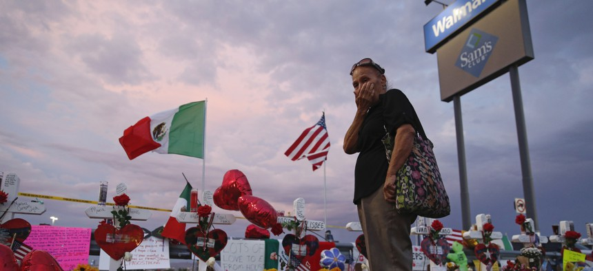 Catalina Saenz wipes tears from her face as she visits a makeshift memorial near the scene of a mass shooting at a shopping complex Tuesday, Aug. 6, 2019, in El Paso, Texas.