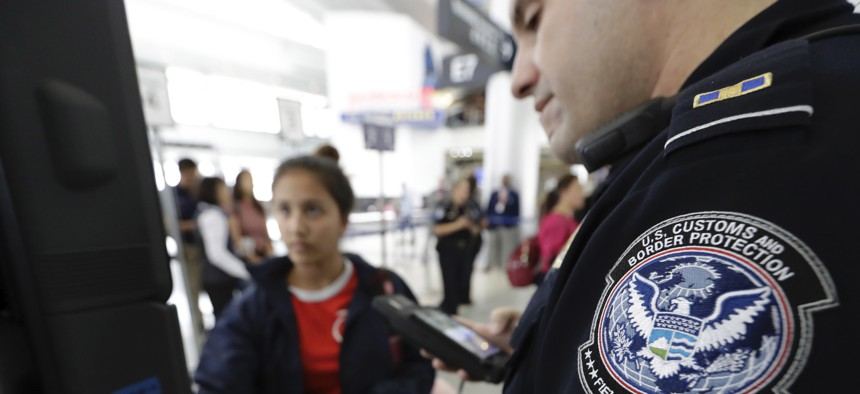 A U.S. Customs and Border Protection officer helps a passenger navigate a new facial recognition kiosk before boarding a flight to Tokyo in 2017 at George Bush Intercontinental Airport, in Houston.