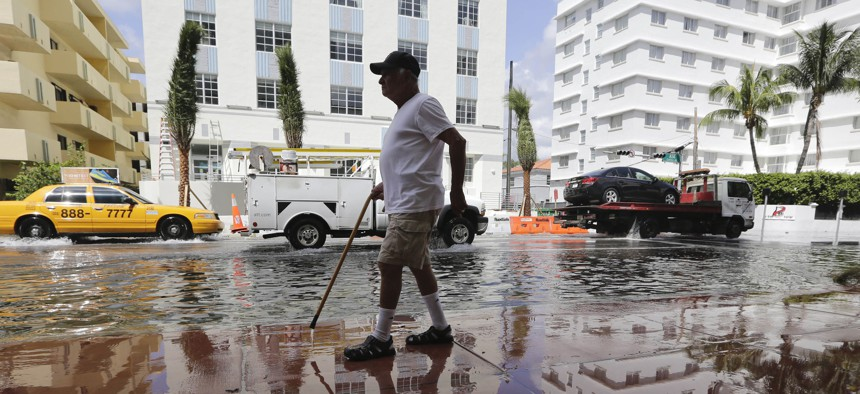 In this 2015 photo, Louis Fernandez walks along a flooded street in Miami Beach, Fla.
