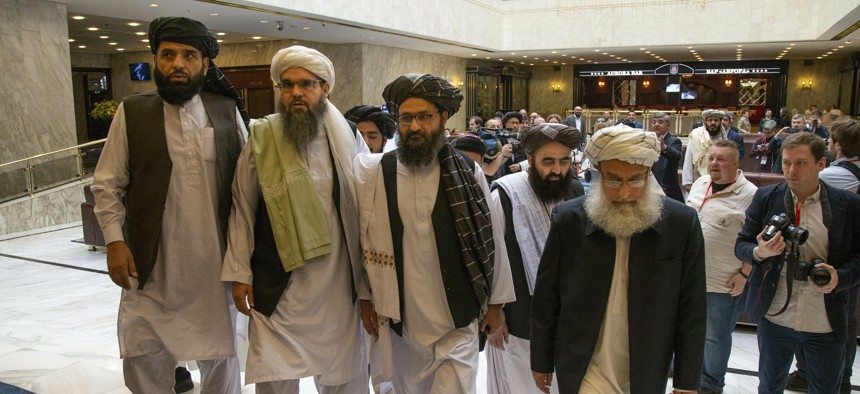 Mullah Abdul Ghani Baradar, the Taliban group's top political leader, third from left, arrives with other members of the Taliban delegation for talks in Moscow, Russia
