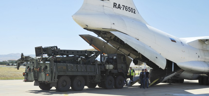 Military officials work around a Russian transport aircraft carrying parts of the S-400 air defense systems, after it landed at Murted military airport outside Ankara on Aug. 27..
