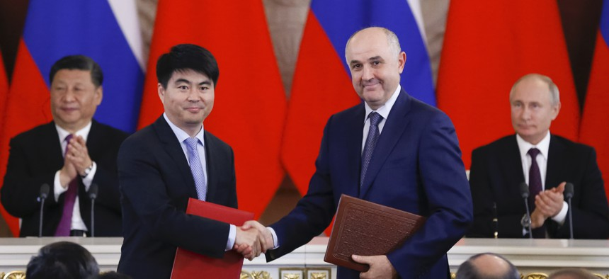 Deputy Chairman of Huawei Guo Ping shakes hands with Alexei Kornya, president of Russia's MTS mobile network operator, at the Kremlin in Moscow on June 5, 2019, as Russian President Vladimir Putin and Chinese President Xi Jinping look on.