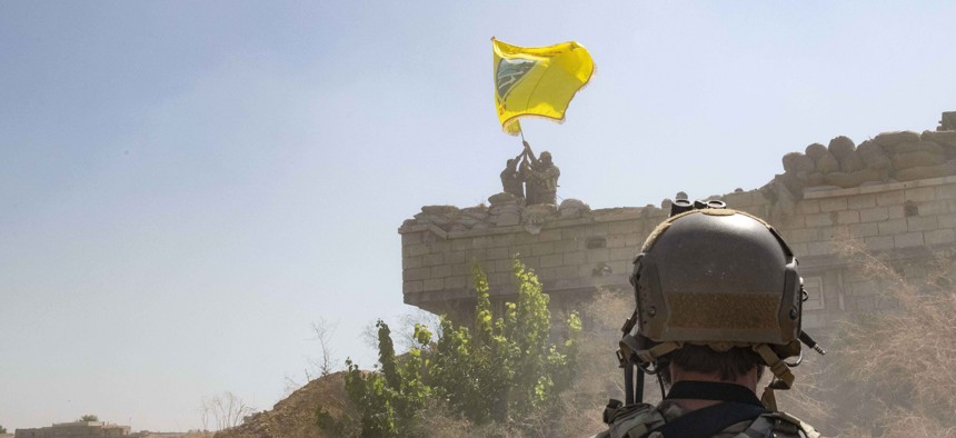 """In this Sept. 21, 2019, photo,  a U.S. soldier watches the Syrian Democratic Forces demolish a Kurdish fighters' fortification and raise a Tal Abyad Military Council flag over the outpost as part of the so-called """"safe zone"""" near the Turkish border."""