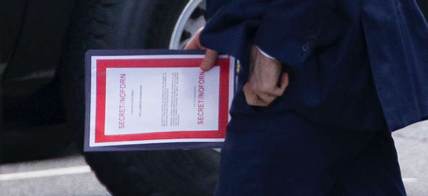 A national-security leader carries a document labeled secret as he arrives for a meeting with President Donald Trump about Iran at the White House on June 20, 2019.