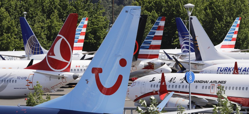 Dozens of grounded Boeing 737 MAX airplanes, including one for TUI Airlines, center, crowd a parking area adjacent to Boeing Field Thursday, Aug. 15, 2019, in Seattle, Washington.