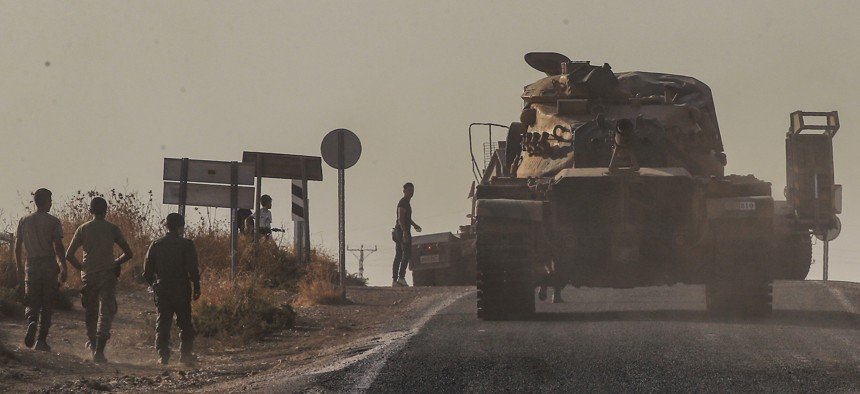 A Turkish forces tank is driven to its new position after was transported by truck, on a road towards the border with Syria in Sanliurfa province, Turkey, on Monday, Oct. 14, 2019.