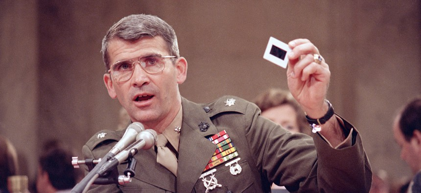 Lt. Col. Oliver North delivers a pro-Contra briefing to the members of the Iran-Contra committee Tuesday, July 14, 1987. North is holding each of the 57 slides and describing what they showed.