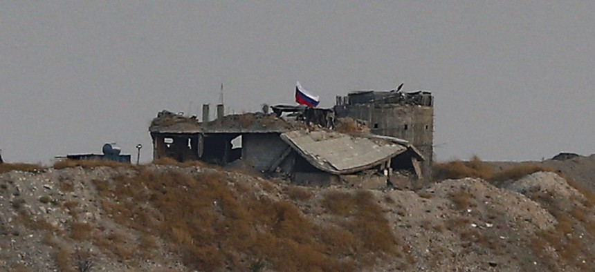 In this photo taken from the Turkish side of the border between Turkey and Syria, in Karkamis, Gaziantep province, southeastern Turkey, a Russian flag is hoisted on a damaged building near the Syrian town of Zor Mahar, Thursday, Oct. 17, 2019.