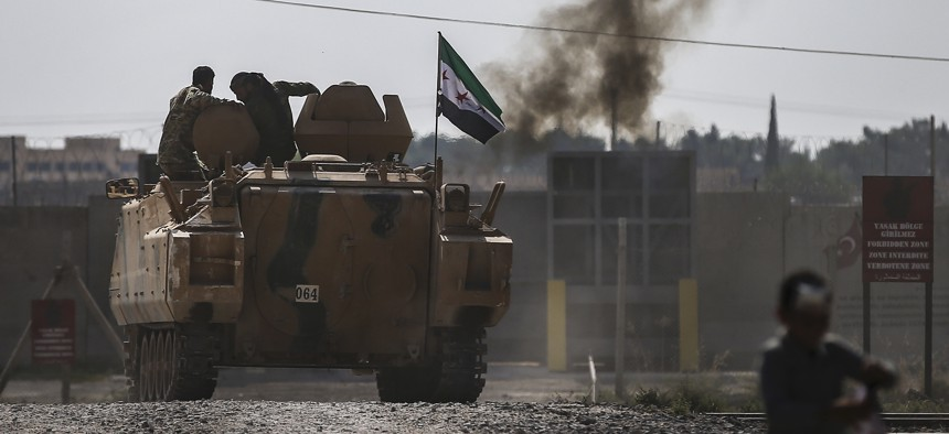 Turkish-backed Syrian opposition fighters on an armoured personnel carrier drive to cross the border into Syria, in Akcakale, Sanliurfa province, southeastern Turkey, Friday, Oct. 18, 2019.