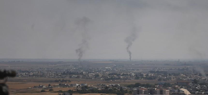 A hilltop in Ceylanpinar, Sanliurfa province, southeastern Turkey, overlooks smoke billowing from fires in Ras al-Ayn, Syria, Sunday, Oct. 20, 2019.