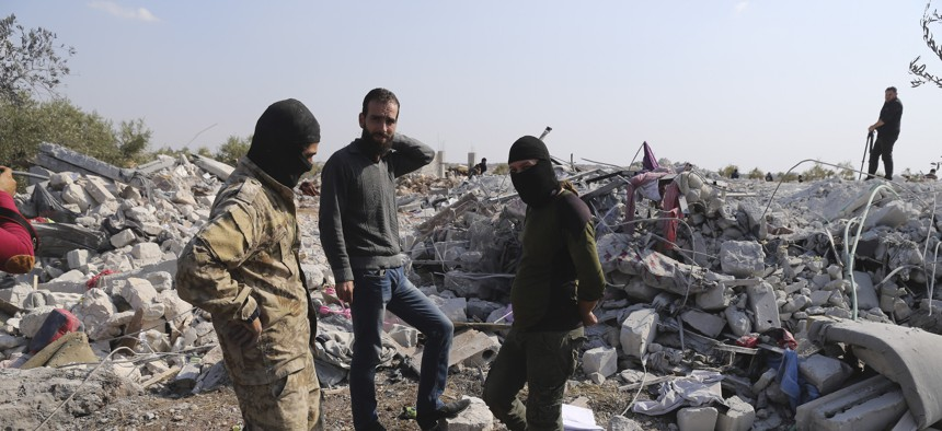 People look at a destroyed houses near the village of Barisha, in Idlib province, Syria, Sunday, Oct. 27, 2019, after an operation by the U.S. military which targeted Abu Bakr al-Baghdadi, the shadowy leader of the Islamic State group.