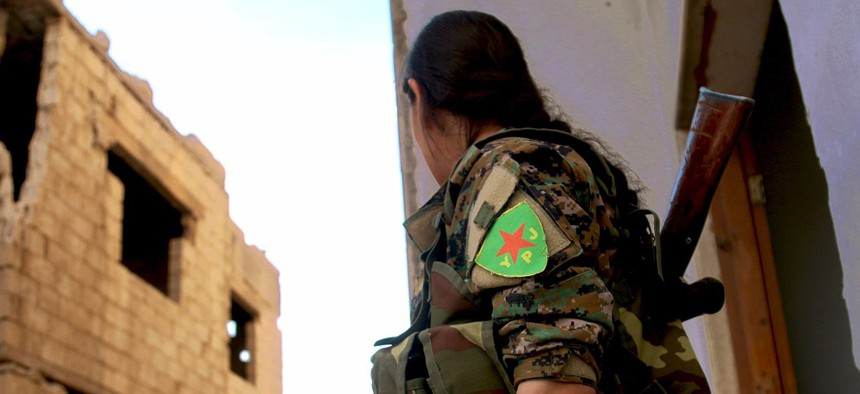 A YPJ fighter looks around a corner in this undated file photo.