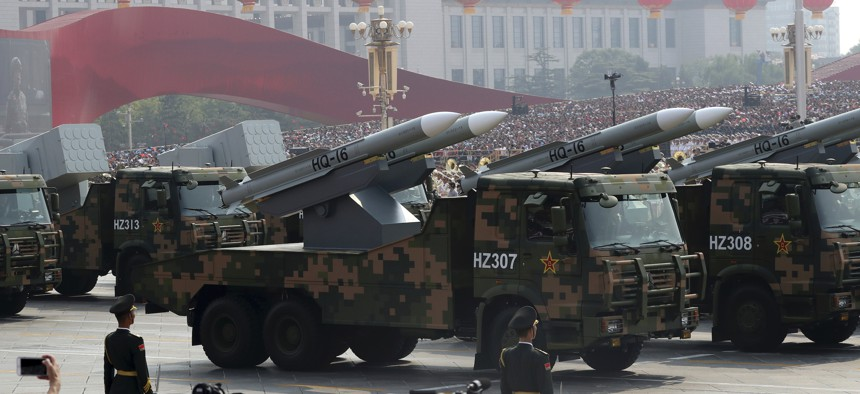 Military vehicles roll down as members of a Chinese military honor guard march during the celebration to commemorate the 70th anniversary of the founding of Communist China in Beijing, Tuesday, Oct. 1, 2019.