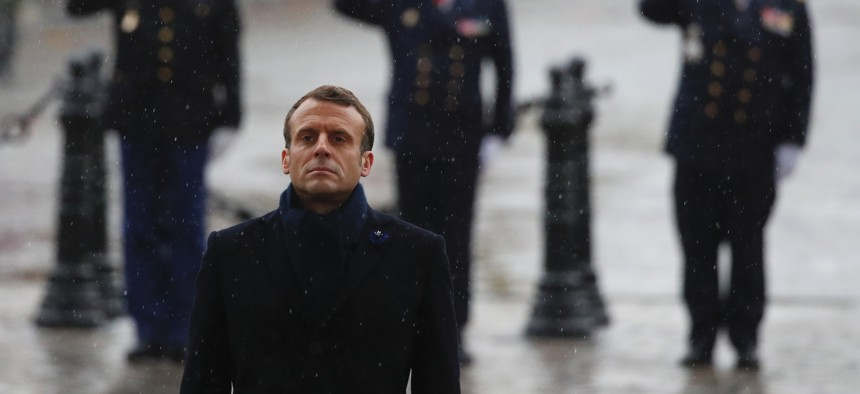 French President Emmanuel Macron stand at attention at the Arc de Triomphe during commemorations marking the 101st anniversary of the 1918 armistice.