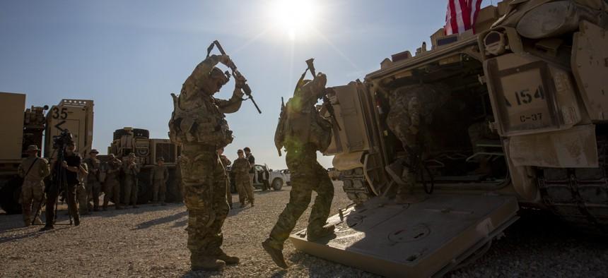 Crewmen enter Bradley fighting vehicles at a US military base in northeastern Syria, Monday, Nov. 11, 2019.