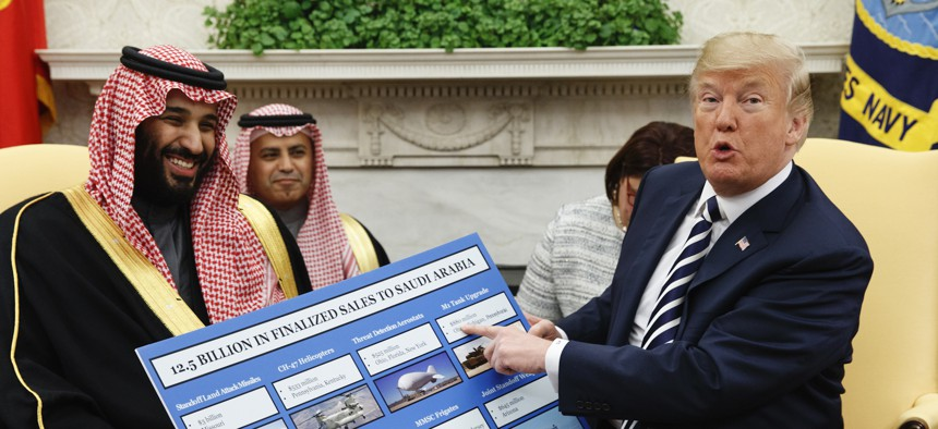 President Donald Trump shows a chart highlighting arms sales to Saudi Arabia during a meeting with Saudi Crown Prince Mohammed bin Salman in the Oval Office of the White House in Washington on March 20, 2018.