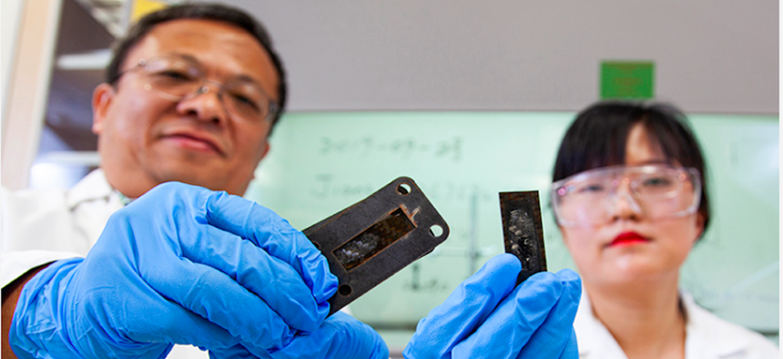 Professor Zhiyong (Richard) Liang and research faculty member Ayou Hao holding pieces of carbon fiber reinforced polymer composites with a protective heat shield made of a carbon nanotube sheet that was heated to a temperature of 1,900 degrees Celsius.
